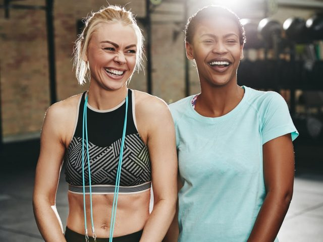 laughing-young-female-friends-standing-in-a-gym-together.jpg
